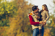 Father carrying his little daughter in a park on an autumn day - CHAF001153