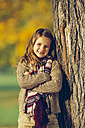 Portrait of smiling girl leaning on tree trunk - CHAF001154