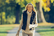 Portrait of smiling woman wearing warm clothes walking in a park - CHAF001084