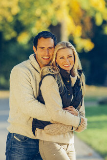 Portrait of couple embracing each other in a park - CHAF001260