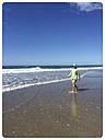 New Zealand, North Island, Waihi Beach, Woman strolling along beach - GWF004385