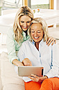 Happy mother and adult daughter using digital tablet at home - CHAF001091