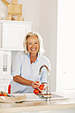 Smiling mature woman washing tomatoes at kitchen sink - CHAF001098
