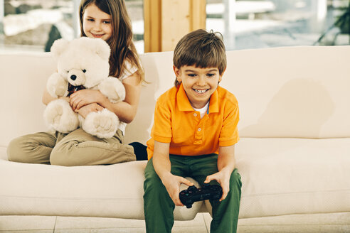 Boy playing video game in living room with sister holding teddy bear - CHAF001558