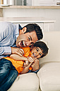Playful father and son on sofa - CHAF001114