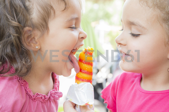Two little sisters eating together a popsicle - ERLF000005 - Enrique Ramoz/Westend61