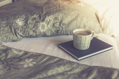Book and cup of white coffee on a bed - ASCF000320