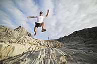 Spain, Valdovino, young man jumping in the air in rocky landscape - RAEF000307