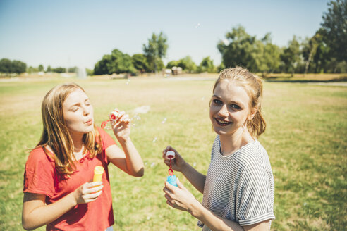 Two teenage girls blowing soap bubbbles in park - AIF000042