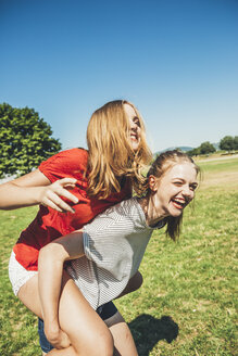 Carefree teenage girl carrying friend piggyback in park - AIF000045