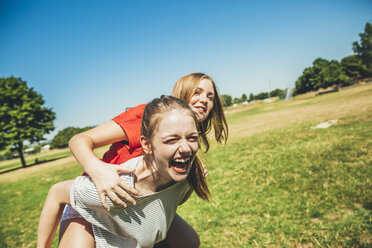 Carefree teenage girl carrying friend piggyback in park - AIF000048