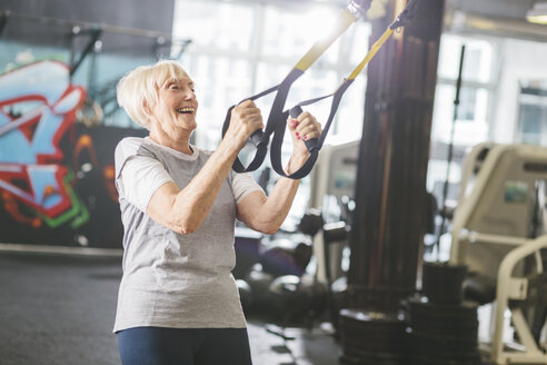 Happy senior woman in gym doing suspension training - MADF000519