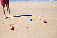 Boy standing on the beach playing boccia - GEMF000314