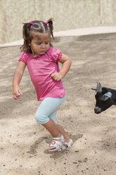 Little girl running away from a goat - ERLF000010