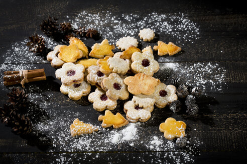 Different Christmas cookies and spices on black wood - MAEF010982