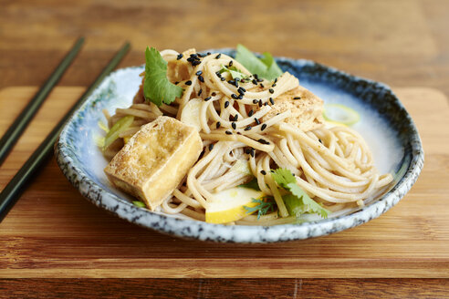 Asian noodle salad with soba noodles, tofu, green onions, yellow zucchini and coriander, garnished with black sesame seeds - HAWF000827