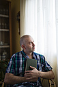 Pensive man with book at home - RAEF000327