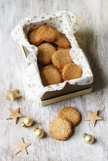Box of whole grain cocos cookies and Christmas decoration on wood - EVGF002076