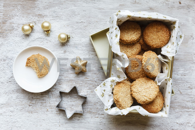 Box of whole grain cocos cookies, Christmas decoration and cookie cutter on wood - EVGF002087