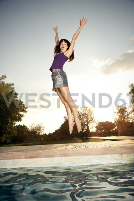 Exuberant young woman jumping at the poolside - TOYF001084