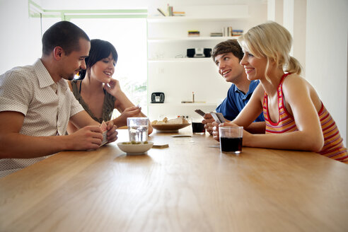 Four friends playing cards at home - TOYF001117