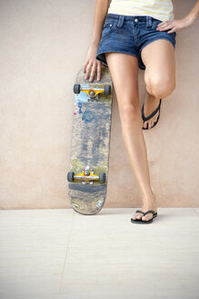 Legs of young woman with longboard in front of a wall - TOYF001137