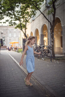 Germany, Berlin, little girl wearing ligh blue summer dress watching soap bubbles - OPF000070