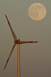 Germany, full moon at evening twilight with wind wheel in the foreground - UMF000788