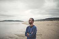 Spain, Ferrol, portrait of smiling man with arms crossed on the beach - RAEF000337