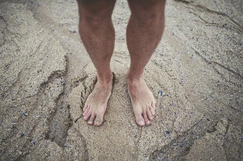 Man's bare feet in the sand on the beach - RAEF000338
