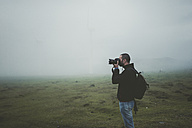 Spain, Ortigueira, photographer taking pictures on a meadow with fog - RAEF000342