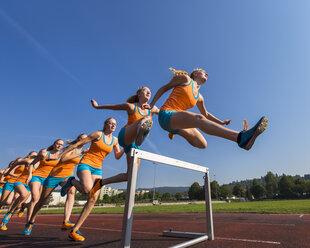 Multiple image of female hurdler jumping over hurdle - STSF000856