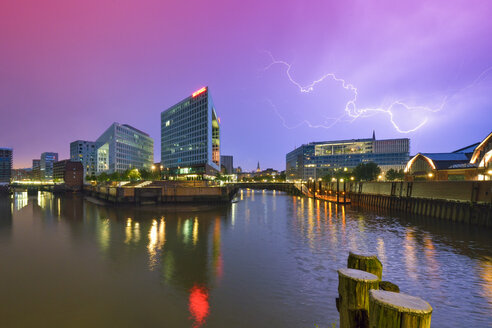 Germany, Hamburg, office buildings and publishing house Der Spiegel at the Ericusspitze during a thunderstorm in the evening - RJ000487