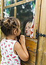 Spain, Asturias, Gijon, Little girls playing through a glass window - MGOF000471