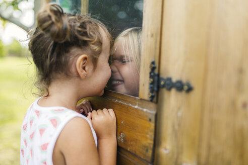 Spain, Asturias, Gijon, Little girls playing through a glass window - MGOF000472