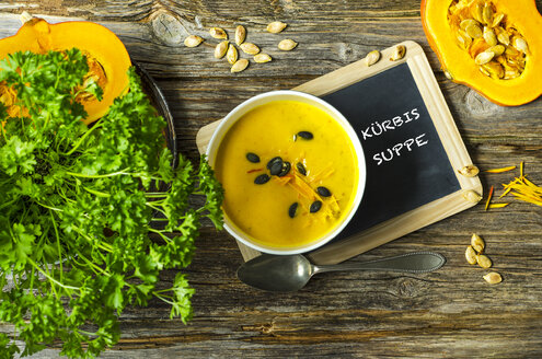 Selfmade pumpkin soup with pumpkin seeds, parsley and a slate on a wooden table - ODF001220
