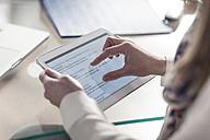 Close-up of person at desk using digital tablet - ZEF007427
