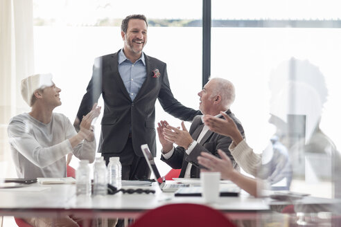 Colleagues applauding for businessman in conference room - ZEF007446