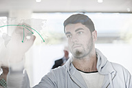 Man drawing on glass in office - ZEF007102