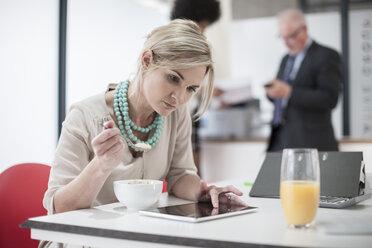 Woman eating breakfast in office - ZEF007109