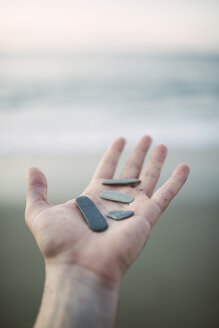 Woman's hand holding pebbles - RAEF000347