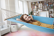 Smiling woman at home lying in hammock - RBF003053