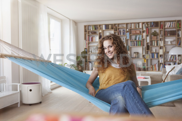 Smiling woman at home sitting in hammock - RBF003057
