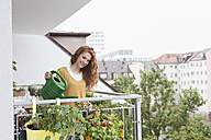 Smiling woman watering flowers on balcony - RBF003062