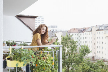 Smiling woman with cup of coffee on balcony - RBF003063
