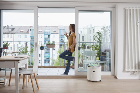 Woman with cup of coffee leaning against balcony door - RBF003124