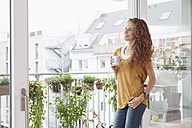 Smiling woman with cup of coffee leaning against balcony door - RBF003066