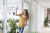 Smiling woman with leaning against balcony door taking a selfie - RBF003127