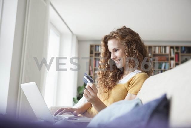 Smiling woman at home shopping online - RBF003082 - Rainer Berg/Westend61