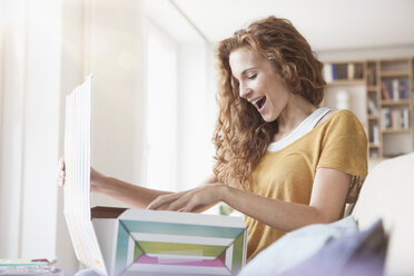 Happy woman at home sitting on couch unpacking parcel - RBF003084